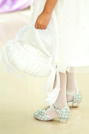 Flower girl carries white flower basket photo