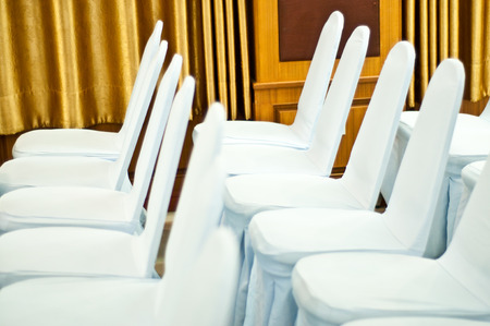White chairs in hall with curtain