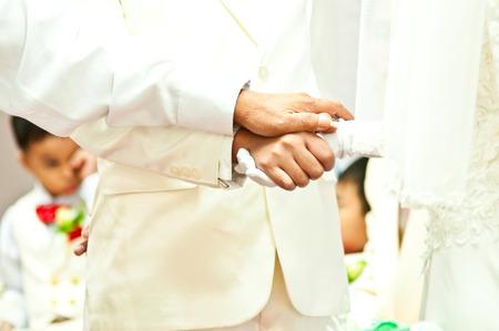 Goom holds brides hand in wedding day