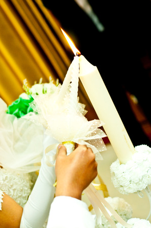 Goom and bride light candle on wedding day