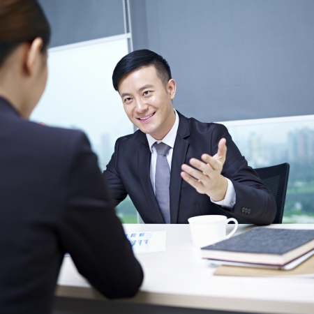 work places: asian business executives having a discussion in office