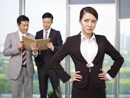 gossip: portret van een jonge Aziatische zakenvrouw met haar collega's in de achtergrond