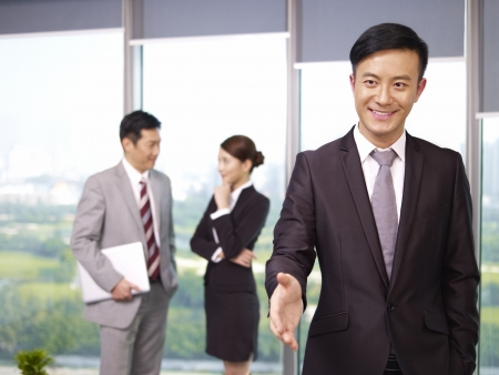 young confident asian business executive reaching out for a handshake  photo