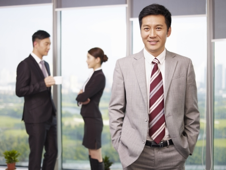 portrait of a senior business executive with his colleagues in the background