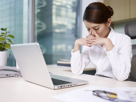 japenese: asian businesswoman sitting and thinking in office, looking tired