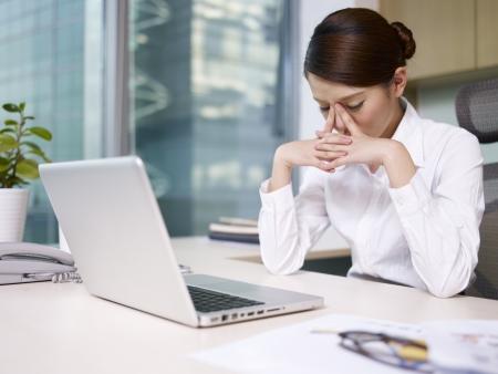 gripe: empresaria asi�tica sentado y pensando en la oficina, con aspecto cansado