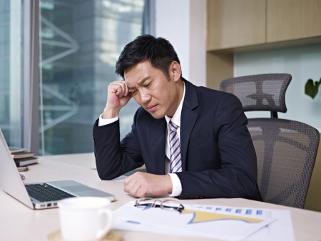 economic depression: asian businessman thinking in office, looking depressed