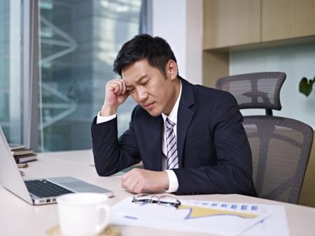 uomo d'affari asiatico pensare in ufficio, guardando depresso photo