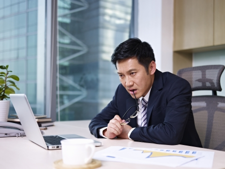 asian businessman sitting and thinking in office  photo