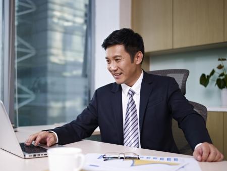 empresario: hombre de negocios asi�ticos que trabajan en la computadora port�til en la oficina