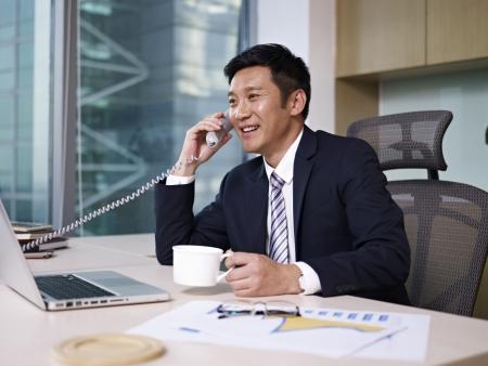 llamando: Hombre de negocios asiático hablando por teléfono en la oficina, mirando feliz