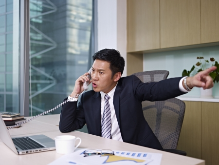 and the horizontal man: asian businessman talking on phone in office, looking angry