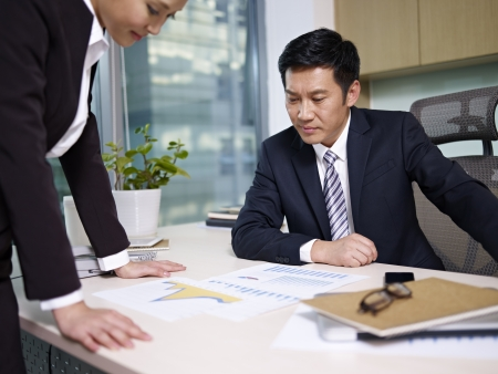 sales executive: asian business people reviewing sales performance in office