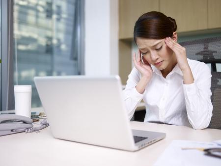 hoofdpijn: Aziatische zakenvrouw zitten en denken in het kantoor, op zoek moe