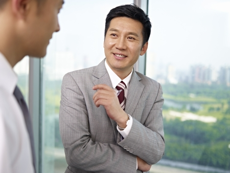 supervisores: hombre de negocios asi�tico de pie y hablando en la oficina