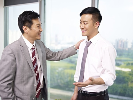 encourage: asian businessman standing and talking in office
