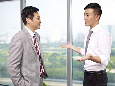 subordinate: asian businessman standing and talking in office