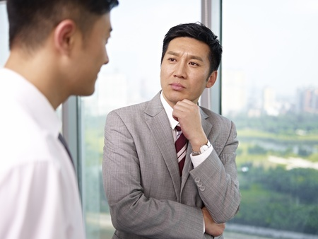 business concern: asian businessman standing and talking in office