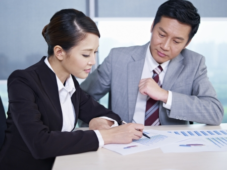 discussing: asian business executives discussing business in office; focus on the woman