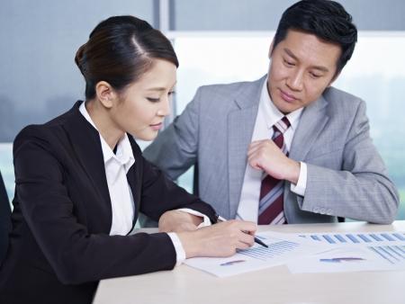 Aziatische zakenlieden bespreken bedrijfsleven in het kantoor, gericht op de vrouw