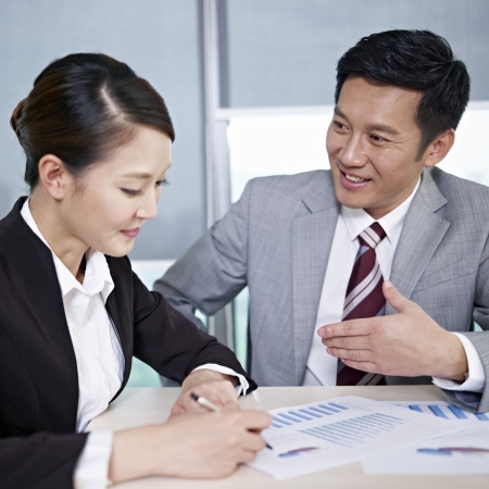 asian business executives discussing business in office; focus on the man  photo