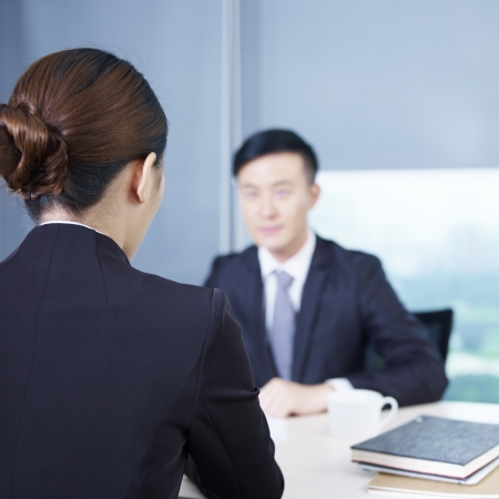 interview: rear view of an interviewer talking to a nervous interviewee  Stock Photo