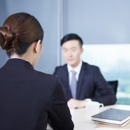 entrevista: vista trasera de un entrevistador habla con un entrevistado nervioso