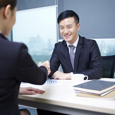 interviewing: asian business executives shaking hands in office