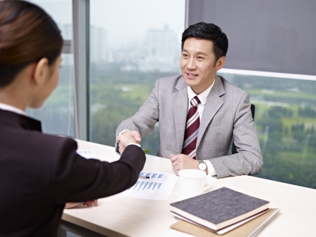 interviewing: a smiling asian business executive shaking hands with his female colleague in office