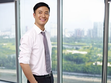looking away: young asian businessman standing by the window in office