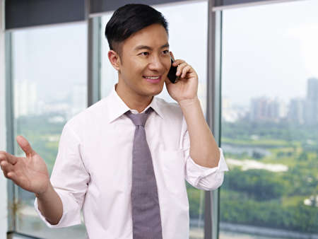 young asian businessman talking on phone in office  Stock Photo - 18194999