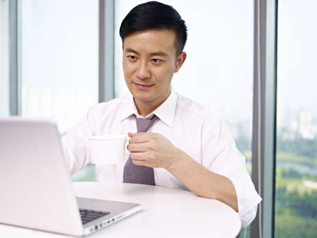 young asian businessman looking at computer and drinking coffee in office  Stock Photo - 18194736