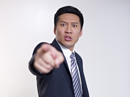 angry hand: angry asian businessman pointing at camera, focus on face