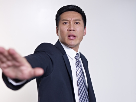 denying: angry asian businessman saying no and gesturing stop, focus on face