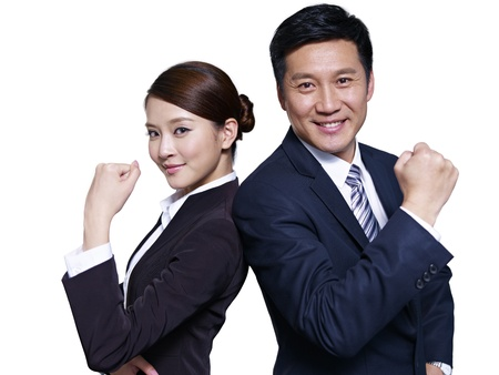 asian businessman and businesswoman standing back to back, making a fist photo