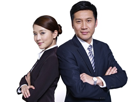 attire: asian businessman and businesswoman standing back to back, arms crossed