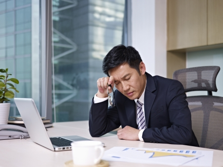 headache: asian businessman sitting in office, looking tired
