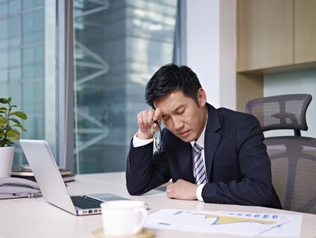 hombre preocupado: Hombre de negocios asi�tico sentado en la oficina, con aspecto cansado