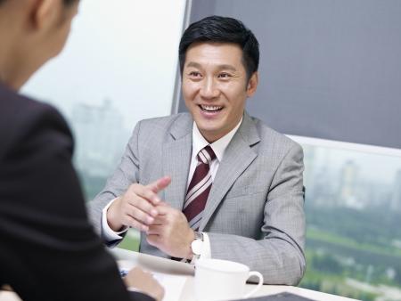 dos personas hablando: gente de negocios asiático hablar de negocios en el cargo