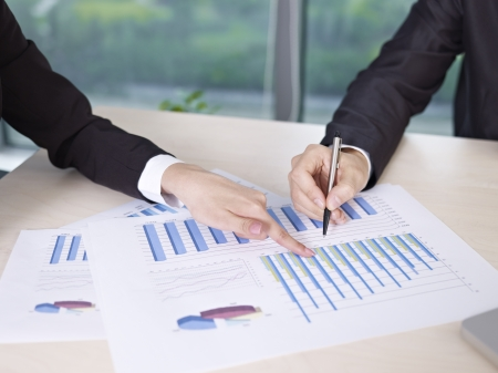 growing business: two business executives analyzing business performance in office  Stock Photo
