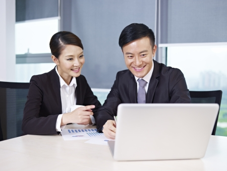 asian on laptop: asian business people discussing business in office  Stock Photo