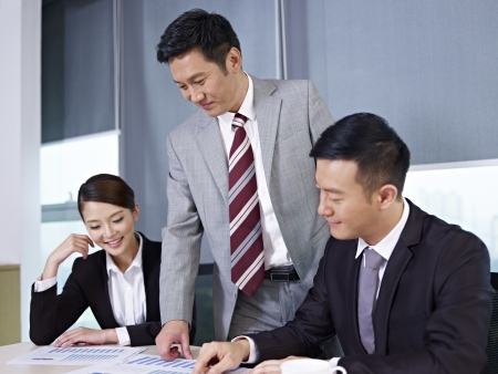 sales meeting: asian business people discussing business in office  Stock Photo