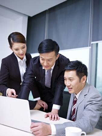 sales executive: a team of asian business people working together in office