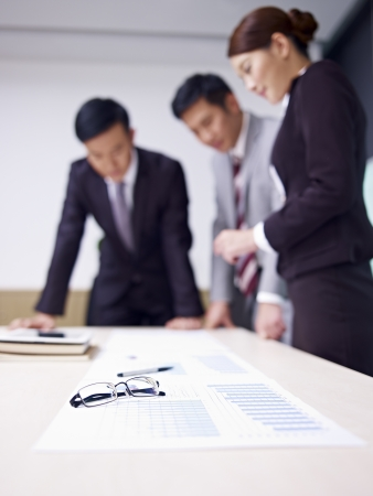 shallow depth of field: a team of asian business people working together in office