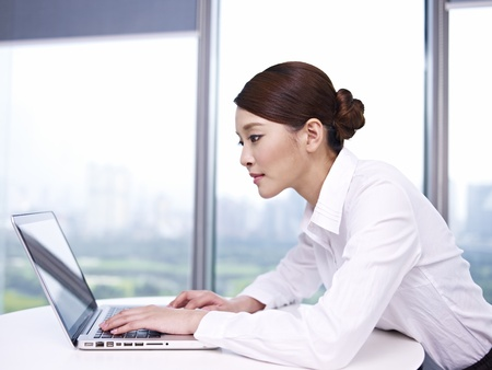 office wear: young asian businesswoman working on laptop in office