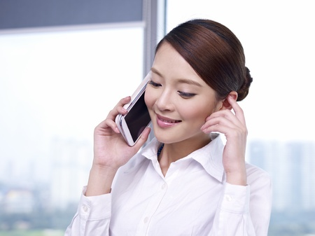 young asian businesswoman talking on cellphone in office  photo