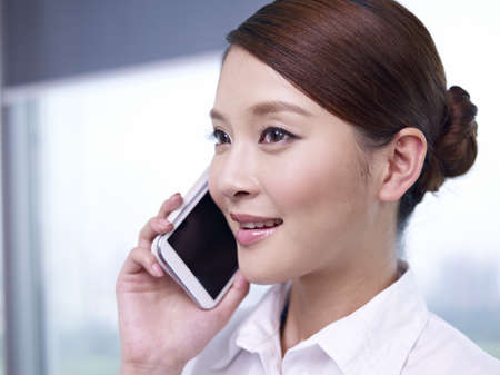 young asian businesswoman talking on cellphone in office  Stock Photo