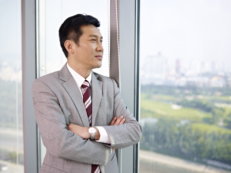 looking forward: asian businessman looking out of window in office