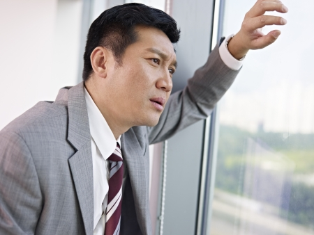 frustrated asian businessman looking out of window in office  Stock Photo