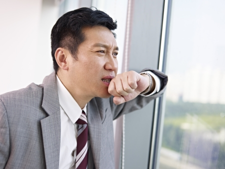 failing: troubled asian businessman looking out of window and thinking in office